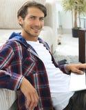 Jeune homme de sourire avec l'ordinateur portable se reposant sur le plancher près du divan Photo stock