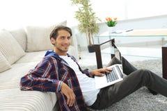 Jeune homme de sourire avec l'ordinateur portable se reposant sur le plancher près du divan Photos libres de droits
