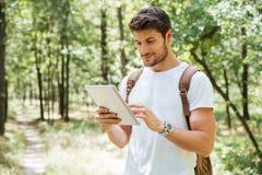 Jeune homme de sourire avec le sac à dos utilisant le comprimé dans la forêt Images stock