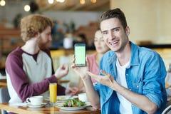 Jeune homme de sourire avec le smartphone Photos libres de droits