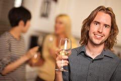 Jeune homme de sourire avec le verre d'avoir une vie sociale de vin Image stock