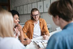 Jeune homme de sourire avec les cheveux blonds et barbe regardant heureusement de côté se reposante avec des amis et discutante q Photo libre de droits