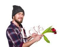 Jeune homme de sourire avec une barbe avec l'amour décoratif de mot et les tulipes rouges d'isolement sur le fond blanc Image libre de droits