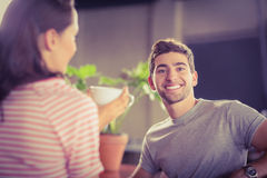 Jeune homme de sourire ayant le café avec son ami Photographie stock