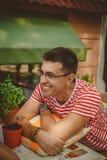 Jeune homme de sourire bel dans le T-shirt rayé blanc et rouge se reposant et détendant au café en plein air de rue Concept de mo Images libres de droits