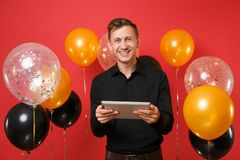 Jeune homme de sourire dans la chemise classique noire tenant et à l'aide de l'ordinateur de PC de comprimé sur les ballons à air photographie stock libre de droits
