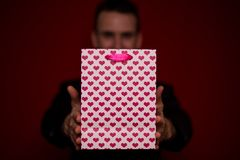 Jeune homme de sourire dans le sac de cadeau d'amour de prise de costume Image libre de droits
