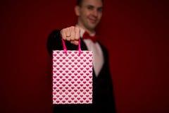 Jeune homme de sourire dans le sac de cadeau d'amour de prise de costume Photos libres de droits