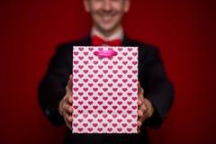 Jeune homme de sourire dans le sac de cadeau d'amour de prise de costume Photos stock
