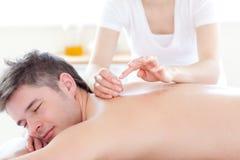 Jeune homme de sourire dans une thérapie d'acuponcture Image stock