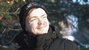 Jeune homme de sourire dans une veste noire regardant loin en plan rapproché de forêt d'hiver banque de vidéos