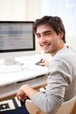 Jeune homme de sourire devant l'ordinateur Image libre de droits