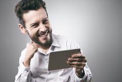Jeune homme de sourire gai avec le comprimé Image stock