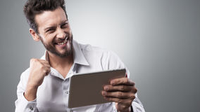 Jeune homme de sourire gai avec le comprimé Photo stock