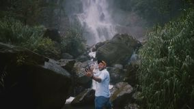 Jeune homme de sourire heureux de blogger de voyage prenant le selfie de smartphone à la cascade tropicale majestueuse épique de  banque de vidéos