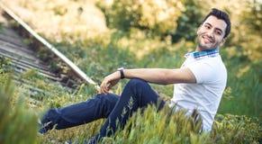 Jeune homme de sourire heureux s'asseyant sur des lignes de train Photographie stock libre de droits