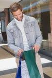 Jeune homme de sourire heureux tenant des paniers et regardant à l'intérieur Photo libre de droits