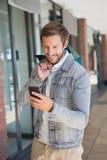 Jeune homme de sourire heureux tenant des paniers et regardant son mobile Photos libres de droits