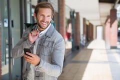 Jeune homme de sourire heureux tenant les paniers et son mobile Image libre de droits