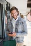 Jeune homme de sourire heureux tenant les paniers et son mobile Photo stock