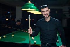 Jeune homme de sourire jouant le jeu de billard Images libres de droits