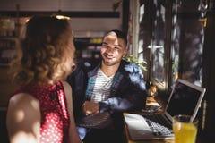 Jeune homme de sourire parlant avec l'ami féminin s'asseyant au café Photographie stock libre de droits