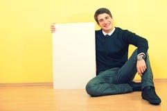 Jeune homme de sourire retenant un panneau-réclame blanc Photos libres de droits