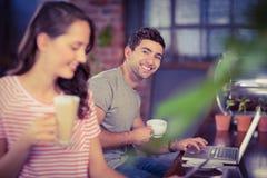 Jeune homme de sourire s'asseyant à la barre et à l'aide de l'ordinateur portable Photographie stock libre de droits