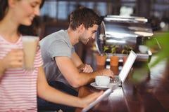 Jeune homme de sourire s'asseyant à la barre et à l'aide de l'ordinateur portable Photo libre de droits