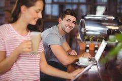 Jeune homme de sourire s'asseyant à la barre et à l'aide de l'ordinateur portable Photos libres de droits
