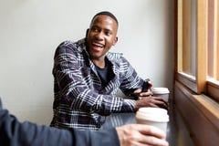 Jeune homme de sourire s'asseyant au café avec un ami Photographie stock