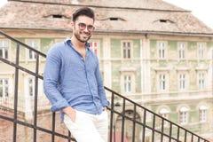 Jeune homme de sourire se tenant sur quelques escaliers de ville Image stock