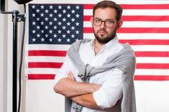 Jeune homme de sourire sur le fond de drapeau des Etats-Unis Photo stock