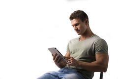 Jeune homme de sourire tenant le lecteur d'ebook, s'asseyant Image stock