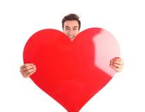 Jeune homme de sourire tenant un grand coeur rouge Image stock