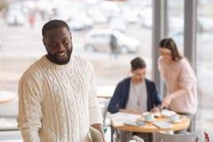 Jeune homme de sourire travaillant avec des collègues dans un café Image libre de droits