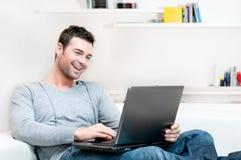 Jeune homme de sourire travaillant sur l'ordinateur portatif Photographie stock