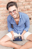 Jeune homme de sourire travaillant sur une tablette Photo stock