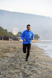 Jeune homme de sport courant dans la séance d'entraînement de forme physique sur la plage le long du début de la matinée de mer Photographie stock