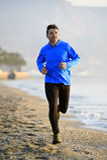 Jeune homme de sport courant dans la séance d'entraînement de forme physique sur la plage le long du début de la matinée de mer Image stock