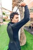 Jeune homme de surfer avec le wetsuit fermant de planche de surf photographie stock