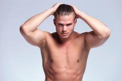 Jeune homme de torse nu avec des mains dans les cheveux Images libres de droits