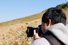 Jeune homme de touristes asiatique prenant une photo avec l'appareil-photo de dslr à l'itinéraire aménagé pour amateurs de la nat Photographie stock libre de droits