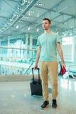 Jeune homme de touristes avec le passeport et carte d'embarquement à l'aéroport prêt à tfly Photographie stock libre de droits