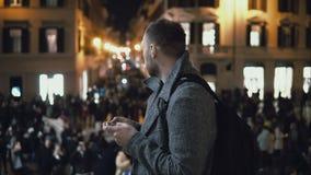 Jeune homme de touristes bel se tenant dans la foule dans la soirée Utilisation masculine le smartphone à la direction de découve Photos stock