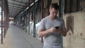 Jeune homme de touristes bel utilisant le téléphone tout en pensant au pilier local à Bangkok banque de vidéos