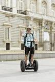 Jeune homme de touristes heureux avec la visite de ville d'équitation de sac à dos segway conduisant le palais de visite heureux  Photos stock