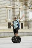 Jeune homme de touristes heureux avec la visite de ville d'équitation de sac à dos segway conduisant le palais de visite heureux  Photographie stock