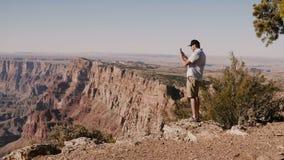 Jeune homme de touristes heureux prenant la photo de smartphone de la position épique de paysage d'été au-dessus de Grand Canyon  clips vidéos