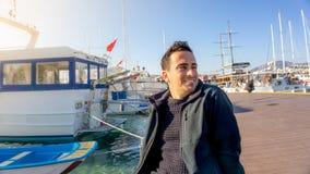 Jeune homme de touristes turc souriant pendant le coucher du soleil dans la marina de Bodrum, Turquie Bateaux à voile, marin, et  photographie stock libre de droits